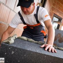 Nakładanie kleju na płyty styropianowe - ocieplanie domu